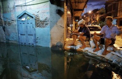 Residents fish from a sandbag barrier built to protect their neighborhood from floods advancing into central Bangkok