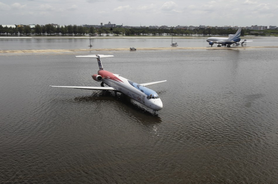 A One-Two-GO Airlines plane is seen parked on a flooded tarmac at Don Muang airport in Bangkok
