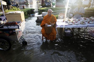 A Buddhist monks waits for morning alms at the flooded market outside the Grand palace in Bangkok