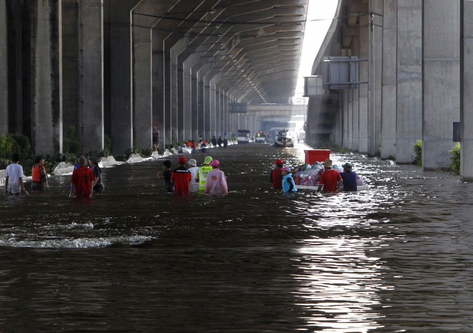People wade through a flooded main street in Bangkok