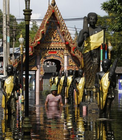 A man wades through a flooded temple in Don Muang district in Bangkok