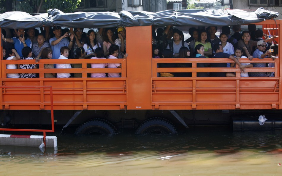 People are evacuated on trucks from a flooded area at Bang Phlat district in Bangkok