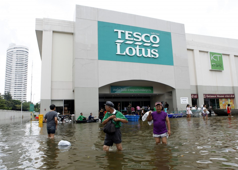 People wades through a flooded Tesco Lotus supermarket after they buy belongings at Bang Phlat district in Bangko