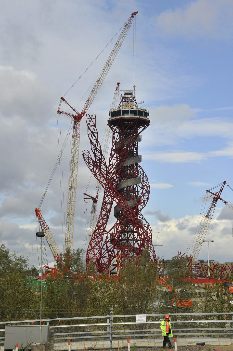 A construction worker passes near the Anish Kapoor-designed ArcelorMittal Orbit tower at the Olympic site at Stratford in east London, on October 7, 2011. The tower will be Britains largest piece of public art and is intended to form part of the legacy o