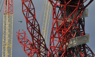 A helicopter flies near the Anish Kapoor-designed ArcelorMittal Orbit tower at the Olympic site at Stratford in east London, on October 7, 2011.