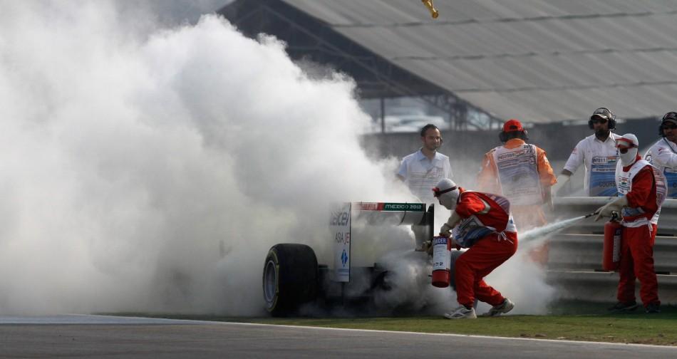 Course marshals use fire extinguishers on the car of Sauber Formula One driver Kamui Kobayashi