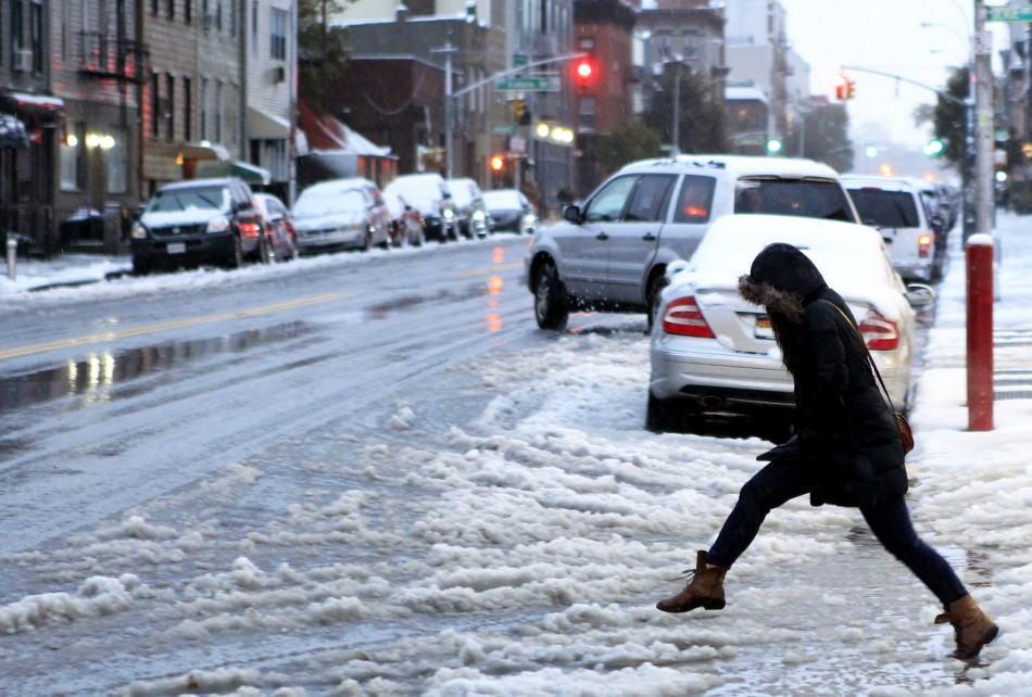 A woman tries to jump over a puddle during an early snow storm in New York