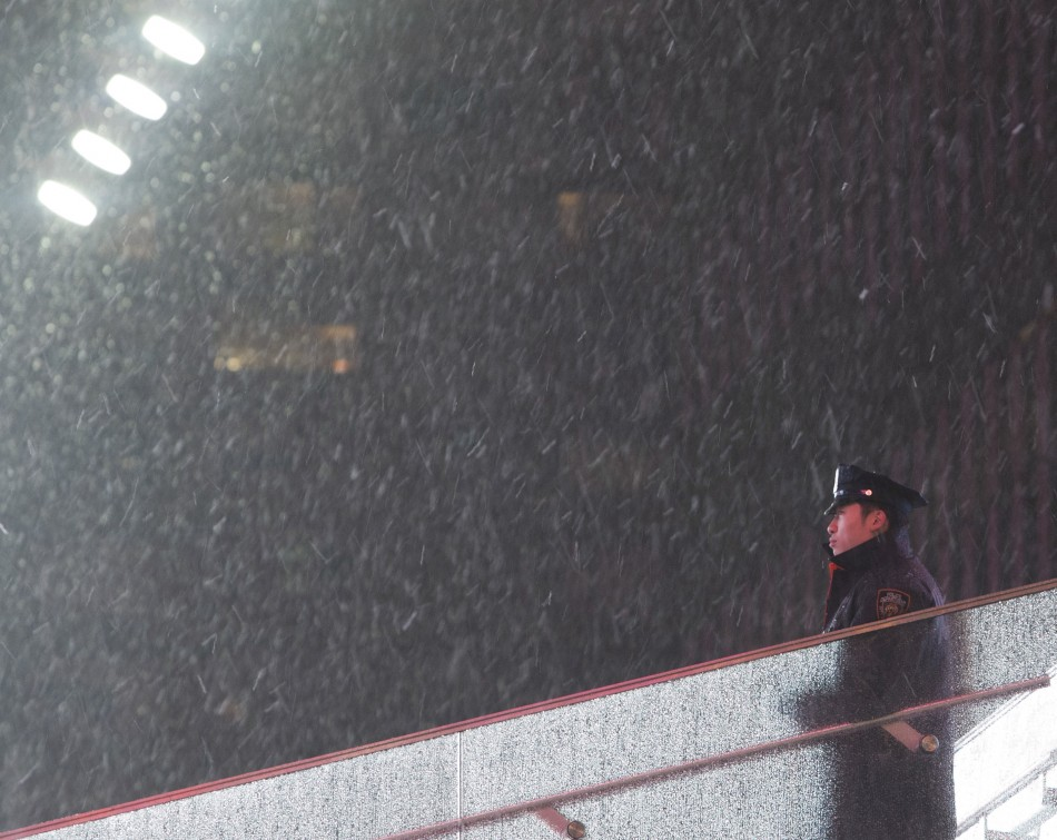 An New York Police Department NYPD officer stands guard at Times Square as snow falls