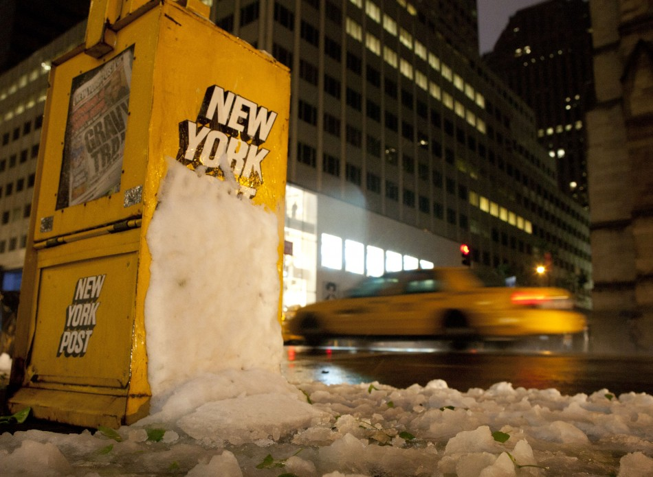 A taxi traverses down Fifth Avenue past a newsstand hit by snow in New York