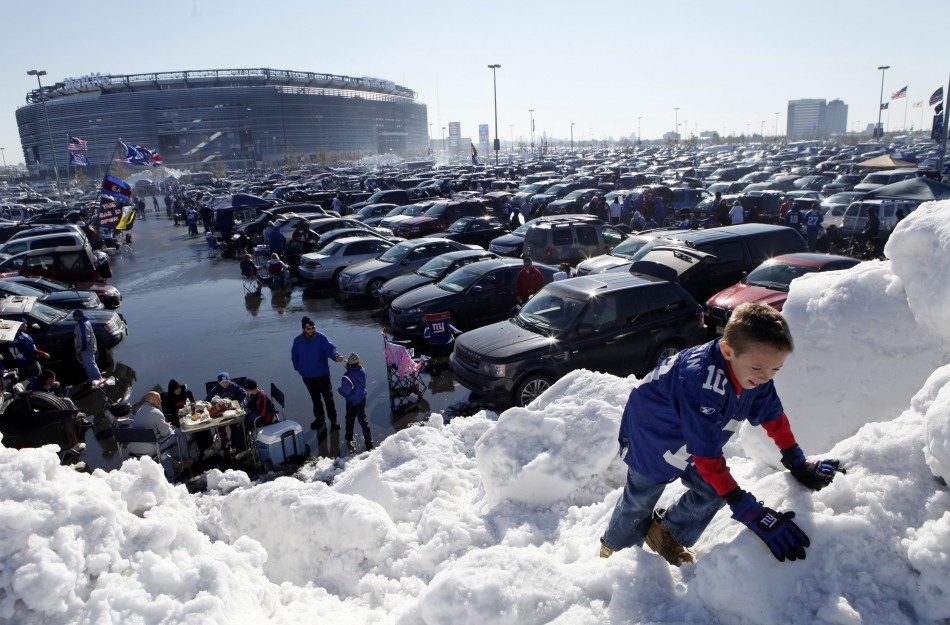 A boy climbs on a giant pile of snow in the parking lot at MetLife Stadium before NFL football game between Giants and Dolphins in East Rutherford