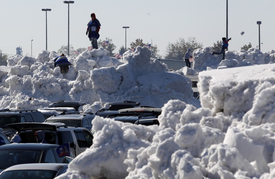 Football fans climb on giant piles of snow in the parking lot at MetLife Stadium before the NFL football game in East Rutherford