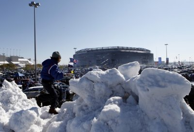 Margaux Lesser from Teaneck, New Jersey, climbs on a giant pile of snow in the parking lot at MetLife Stadium before the NFL football game in East Rutherford