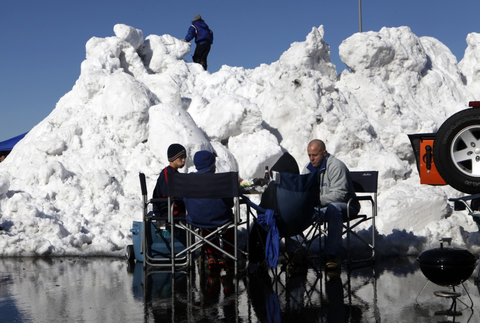 Football fans tailgate in the parking lot near a giant pile of snow at MetLife Stadium before the NFL football game in East Rutherford