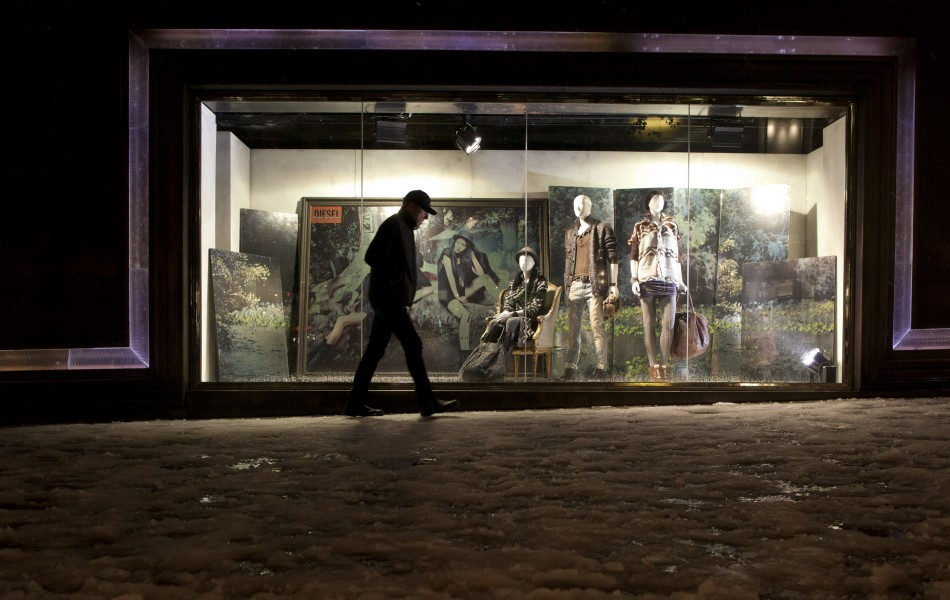 A commuter walks down Fifth Avenue past a store front advertising winter clothing in New York