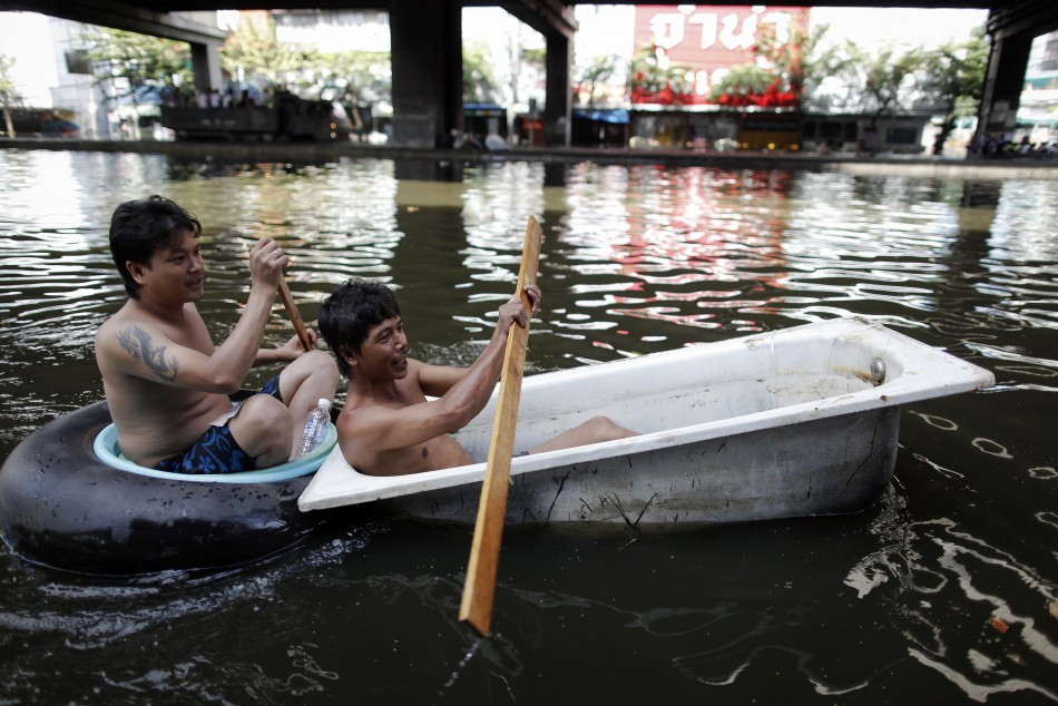 Men paddle their makeshift raft through a flooded street in central Bangkok