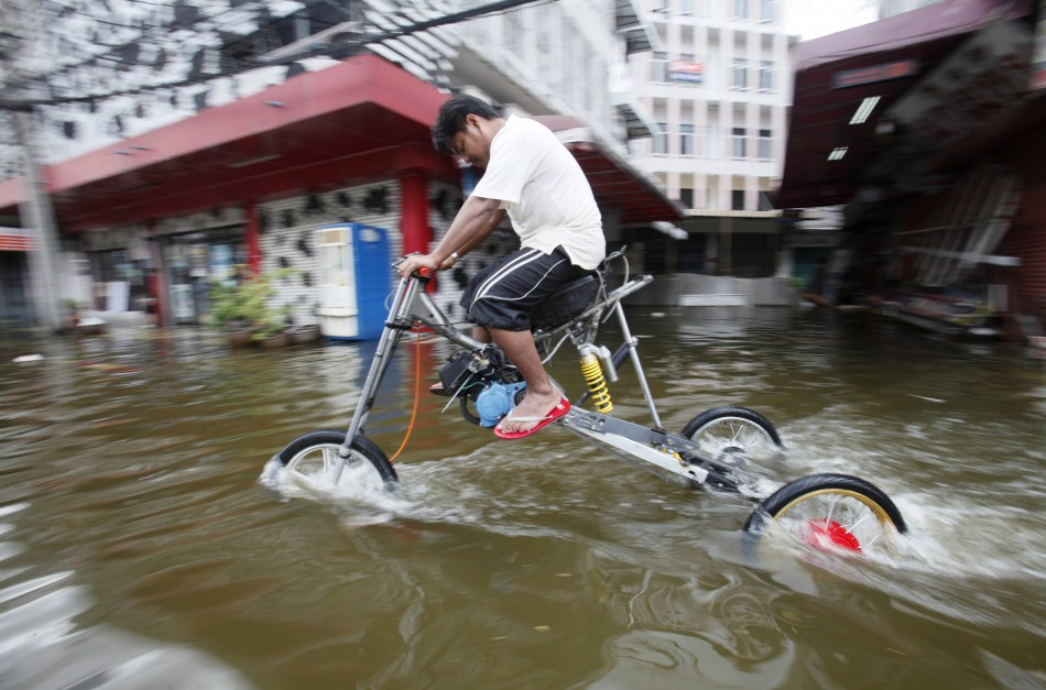 A flood victim cycles through the water using a homemade tall three-wheeler in Bang Phlad district, Bangkok