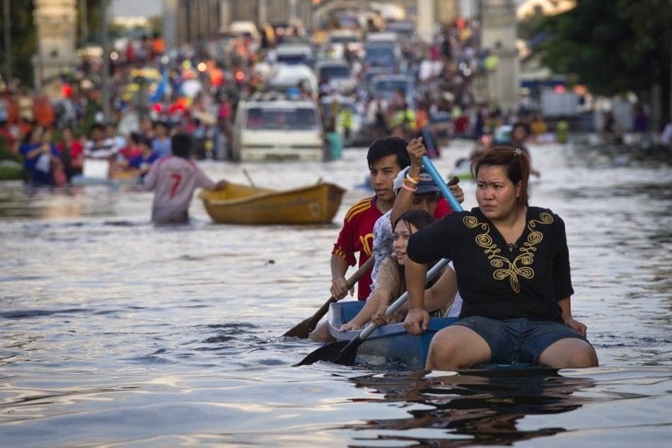 Residents use a boat as transport through a flooded street Bangkok's Bang Phlat district