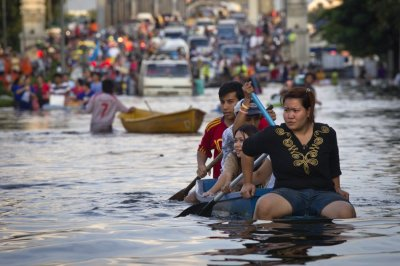 Residents use a boat as transport through a flooded street Bangkoks Bang Phlat district