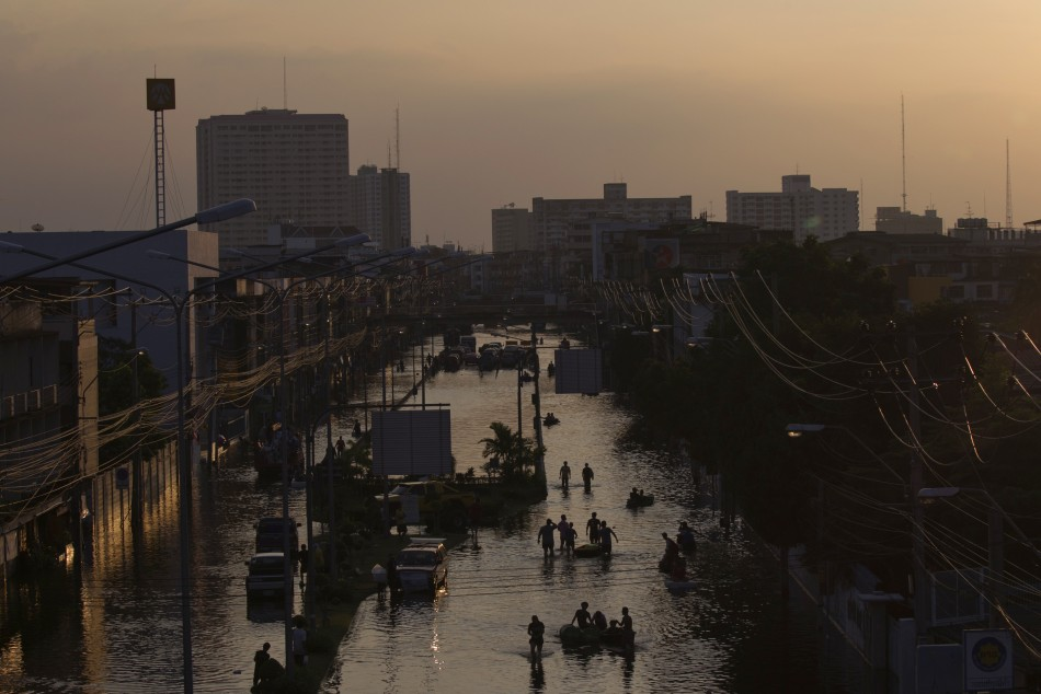 Residents wade through flood waters in Bangkok's Bang Phlat district