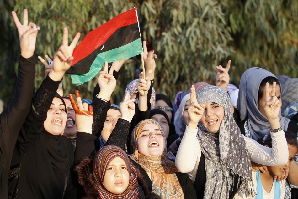Libyans celebrating the return of anti-Gaddafi fighters from Sirte gesture as they welcome them back in Misrata