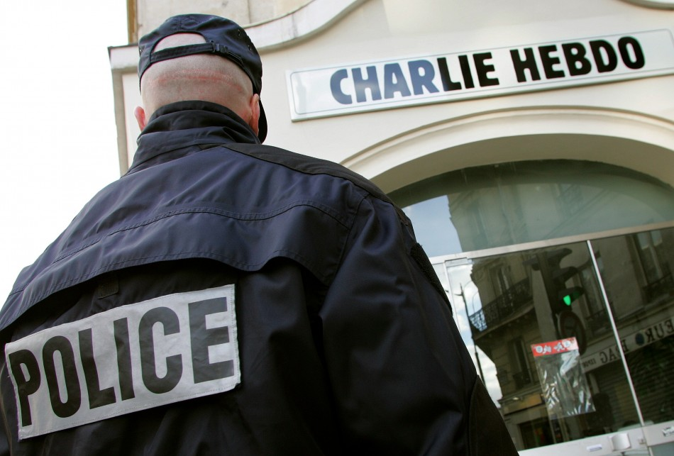 """Policeman stands guard outside French satirical weekly """"Charlie Hebdo"""" in Paris after it published controversial cartoons"""