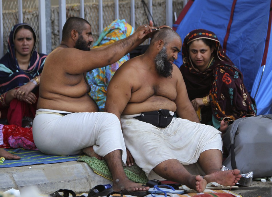 A Muslim pilgrim has his head shaved after casting seven stones in
