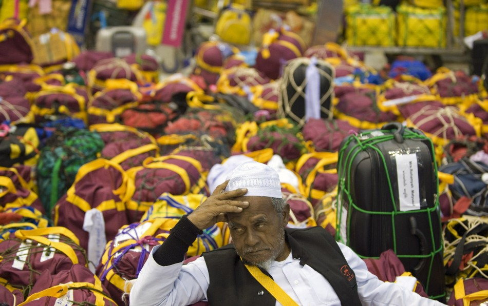 Muslim man from south Thailand sits among bags in the departure hall of Bangkoks Suvarnabhumi Airport