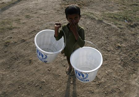 A flood victim carries buckets which he will fill up with water from a hand pump while taking refuge with his family in a relief camp in Sukkur