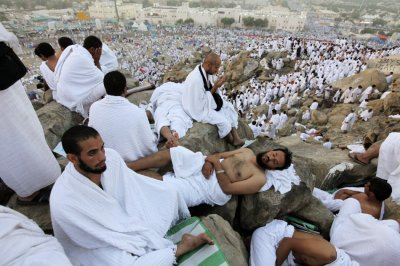 Muslim pilgrims rest as others pray on Mount Mercy on the plains of Arafat