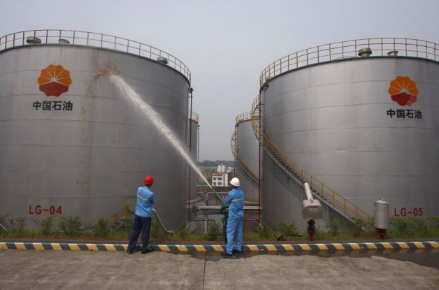 Employees spray water to cool down oil tanks at a PetroChina oil storage facility in Suijing, Sichuan Province, China