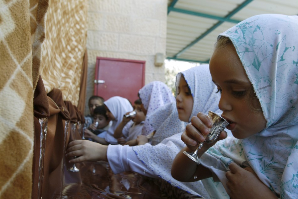 Palestinian schoolchildren drink water as they simulate the annual Muslim pilgrimage of Hajj in Nablus