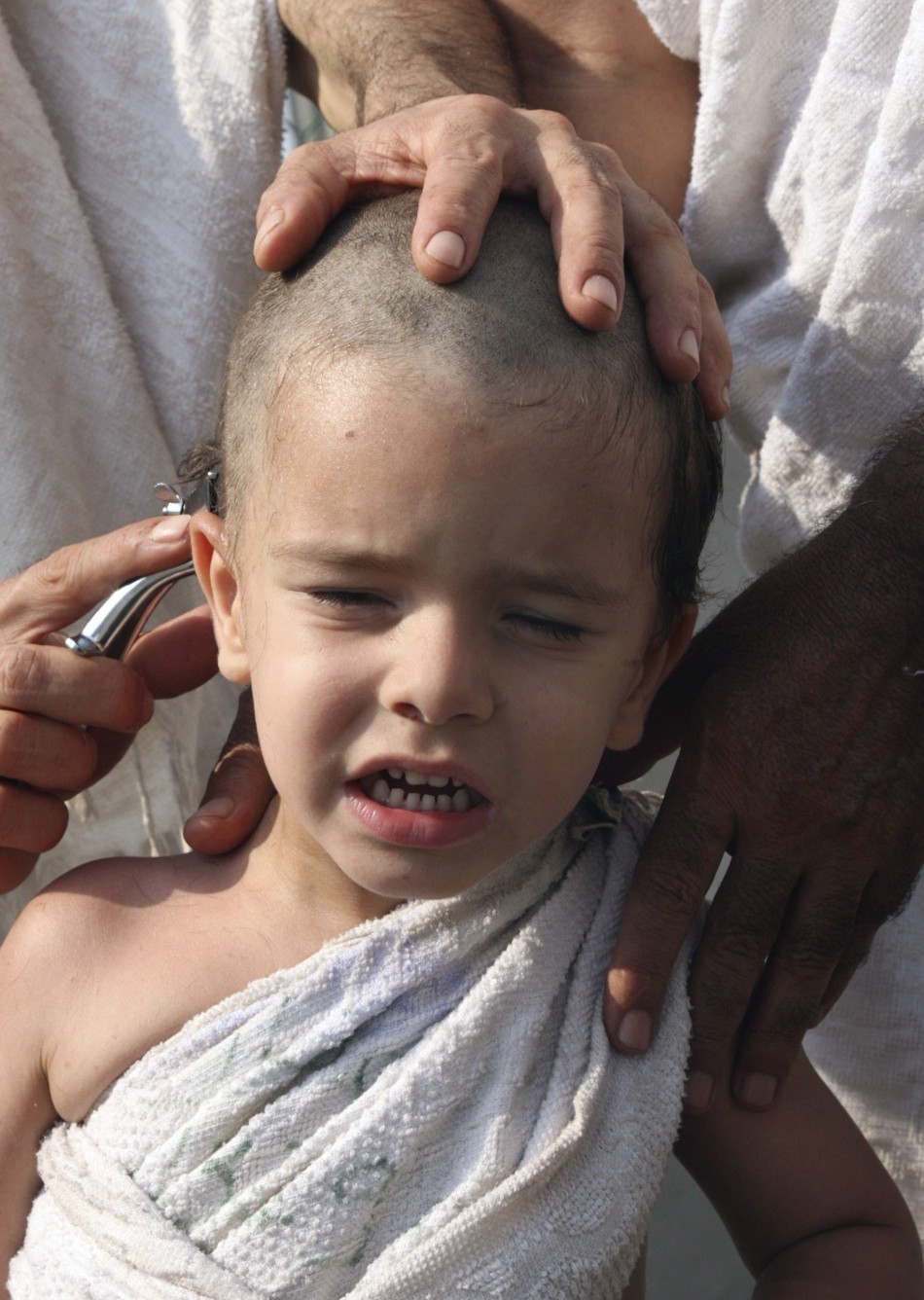 A Muslim pilgrim shaves his son's head during the haj pilgrimage in Mena, outside Mecca