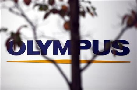 A sign of Olympus Corp is seen behind a tree a outside the company's showroom in Tokyo