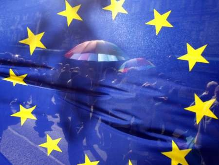 People walk behind the European Union's flag