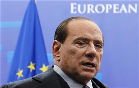 Italy's Prime Minister Silvio Berlusconi talks to the media as he leaves a euro zone leaders summit in Brussels