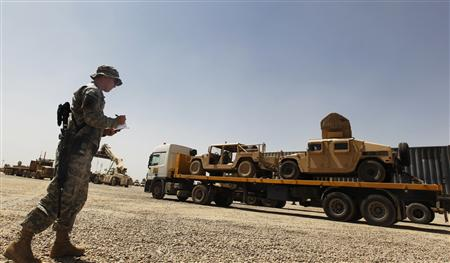 A U.S. Soldier takes down the vehicle numbers of humvees loaded up on a trailer as they prepare to leave Iraq at Balad Base