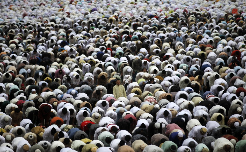 Muslims attend a prayer session along a street in celebration of the Eid al-Adha festival in Jakarta