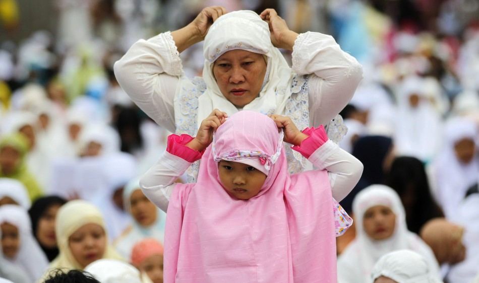 A Muslim women and her daughter prepare to attend a prayer session in celebration of Eid al-Adha in Jakarta