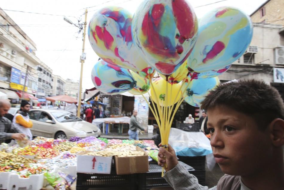 A boy carries balloons for sale ahead of Eid al-Adha in Sidon, Lebanon