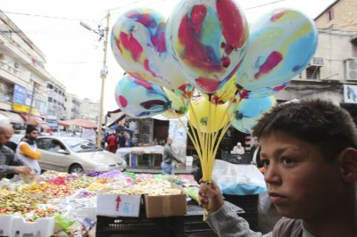 A boy carries balloons for sale ahead of Eid al-Adha in Sidon, Lebanon