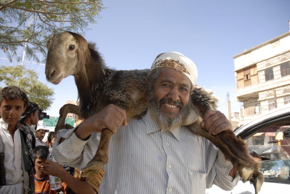A man carries a sacrificial goat on sale at a market, ahead of the Eid al-Adha feast, in Sanaa, Yemen