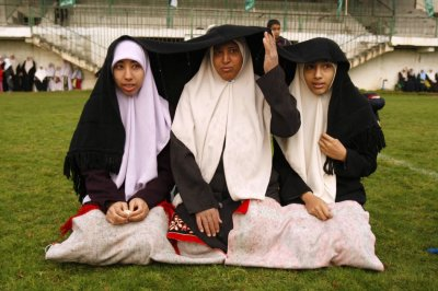 Palestinian women take cover from rain during Eid al-Adha prayers in Gaza City