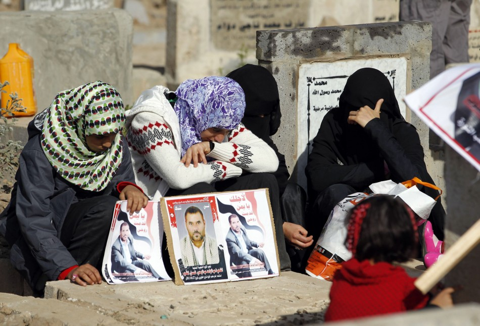 Women react next to their father's grave in a cemetery during the Muslim festival of Eid al al-Adha in Sanaa