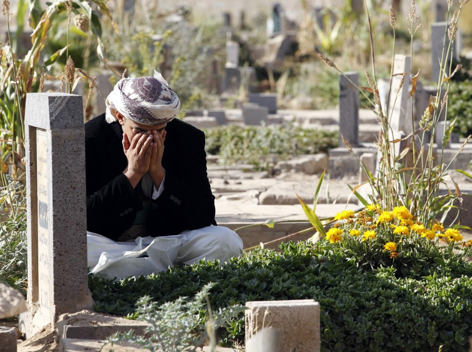A man reacts next to his grave in a cemetery during the Muslim festival of Eid al al-Adha in Sanaa