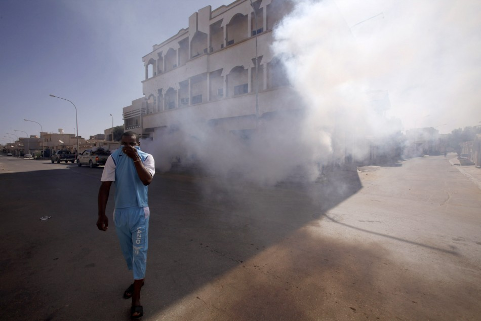 A man covers his face as he walks past a truck spraying smoke to mask the smell of corpses and to ward off insects attracted to the stench in the streets of Sirte City