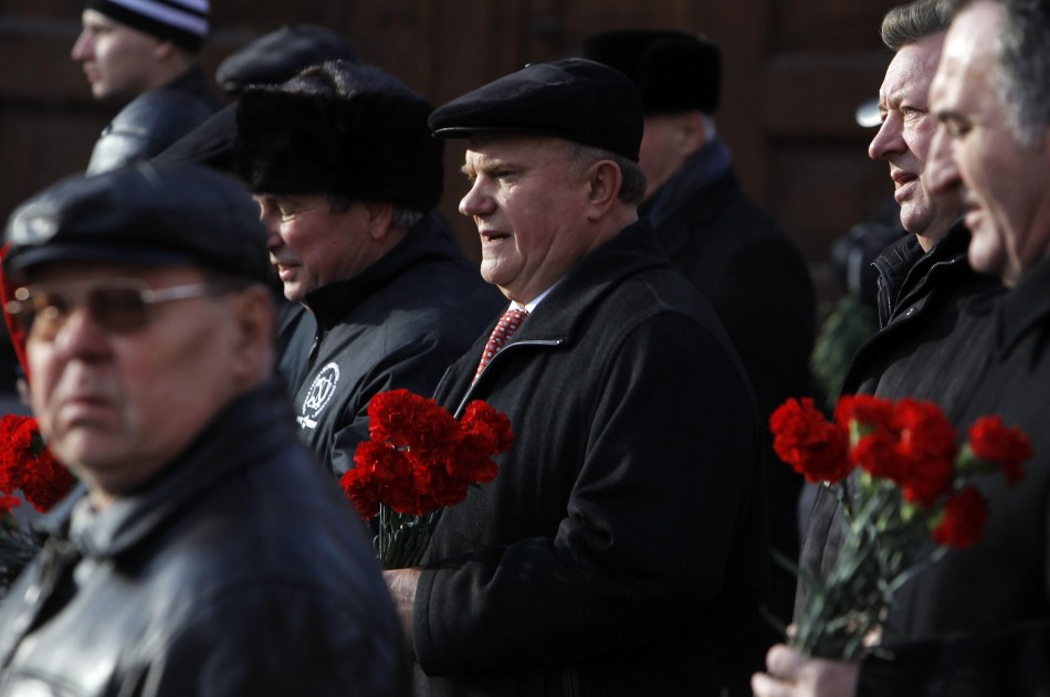 Communist leader Gennady Zuganov holds flowers to put on the graves of prominent Communists on Moscow's Red Square