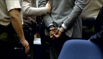 Dr. Conrad Murray is led away in handcuffs into custody of the Los Angeles Sheriffs