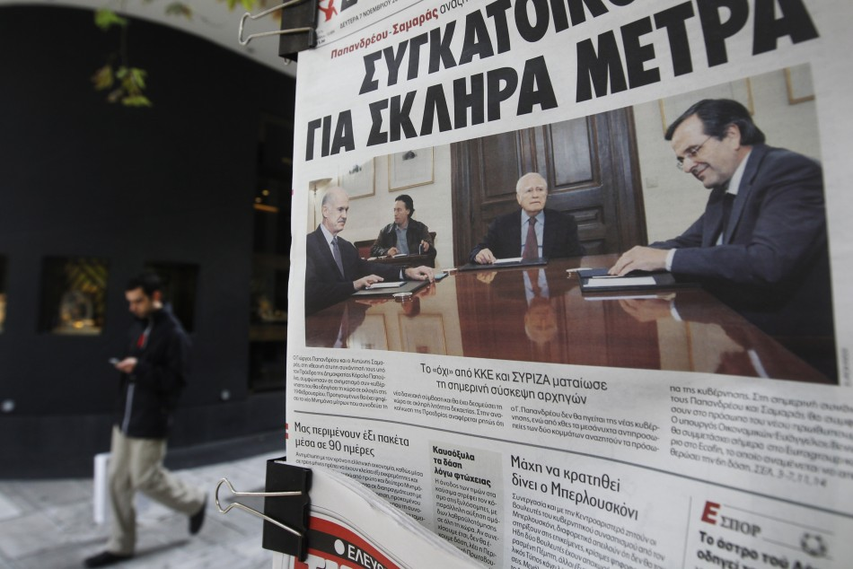 A pedestrian walks past Greek newspapers on sale in Athens November 7, 2011. Greek political leaders were set to choose who will lead a new coalition on Monday and push through a bailout before the country runs out of money in mid-December, with local media tipping former European Central Bank (ECB) deputy head Lucas Papademos for the job