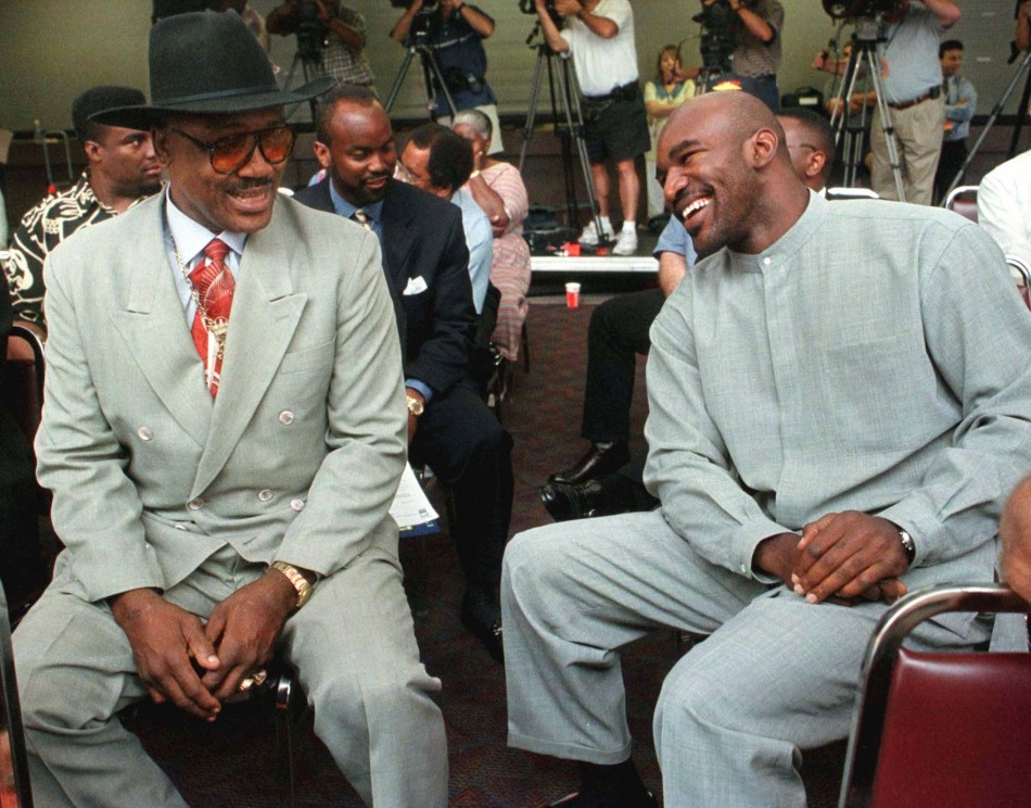 WBA/IBF Heavyweight champion Evander Holyfield (R) chats with former heavyweight champion Joe Frazier (L) prior to a press conference on August 11