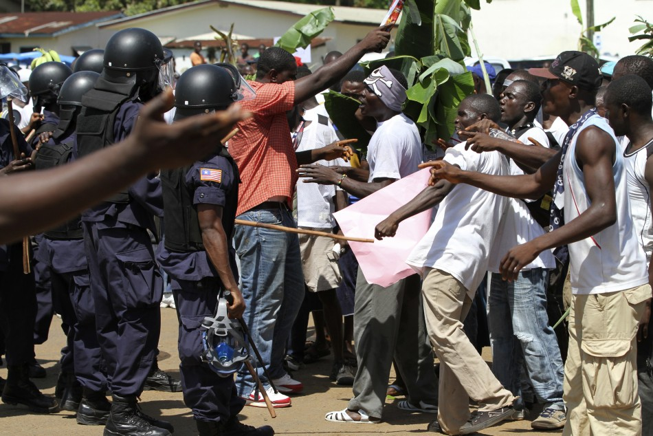 Supporters of presidential challenger Winston Tubman confront riot police as they protest in Monrovia